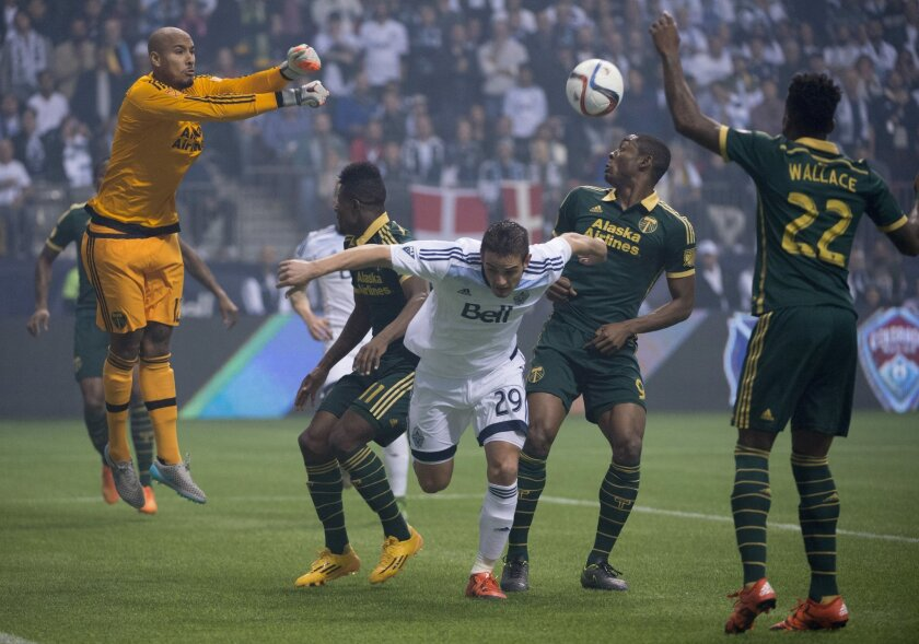 Portland Timbers goalkeeper Adam Larsen Kwarasey (12) stops a shot from the Vancouver Whitecaps FC during the first half of MLS soccer action in Vancouver, British Columbia, Canada, Sunday, Nov. 8, 2015. (Jonathan Hayward/The Canadian Press via AP)