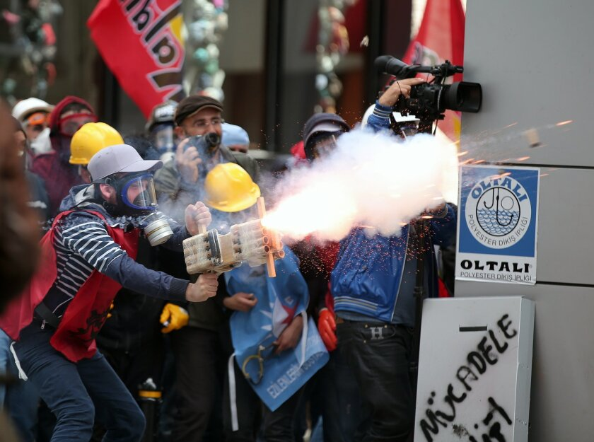 Protesters stand as riot police use water cannons and teargas to disperse thousands of people trying to reach the city's main Taksim Square to celebrate May Day in Istanbul, Turkey, Thursday, May 1, 2014. Clashes erupted between May Day demonstrators and riot police as crowds determined to defy a g