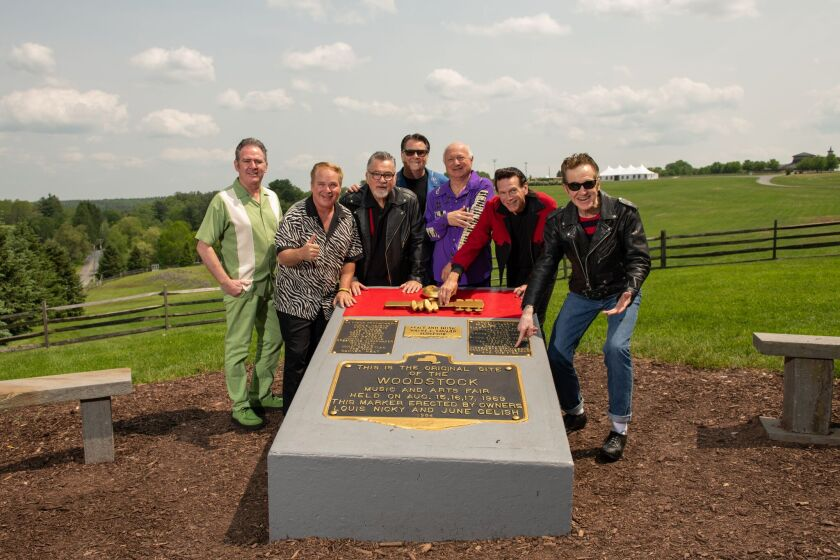 Posing recently at the plaque commemmorating the original Woodstock festival are Sha Na Na members Ty Cox, 'Downtown' Michael Brown, co-founder Jocko Marcellino, Tim Butler, 'Screamin' Scott' Simon (a member since 1970), Randy Hill and co-founder Donny York.