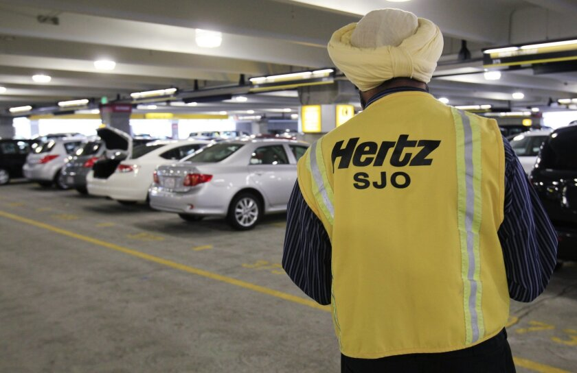 FILE - In this May 9, 2011 file photo, a Hertz rental car worker checks out cars at San Jose International Airport in San Jose, Calif. Hertz on Tuesday, March 18, 2014 said it plans to spin off its equipment rental business into a separate publicly traded company. (AP Photo/Paul Sakuma, File)