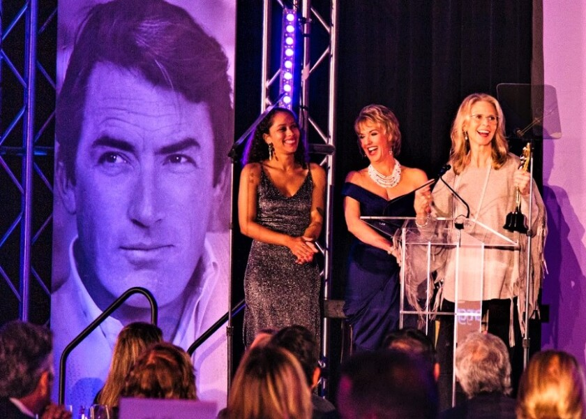 """Actress Lindsay Wagner, far right, holds her San Diego International Film Festival humanitarian award at the 2019 """"Night of the Stars"""" tribute. SDIFF CEO Tonya Mantooth stands next to her with SDIFF's Natalie Barnes, far left. An over-sized portrait of Gregory Peck overlooks the gala audience."""