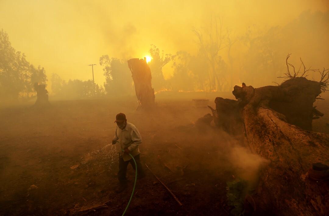 A man shrouded by smoke uses a garden hose to soak dry vegetation