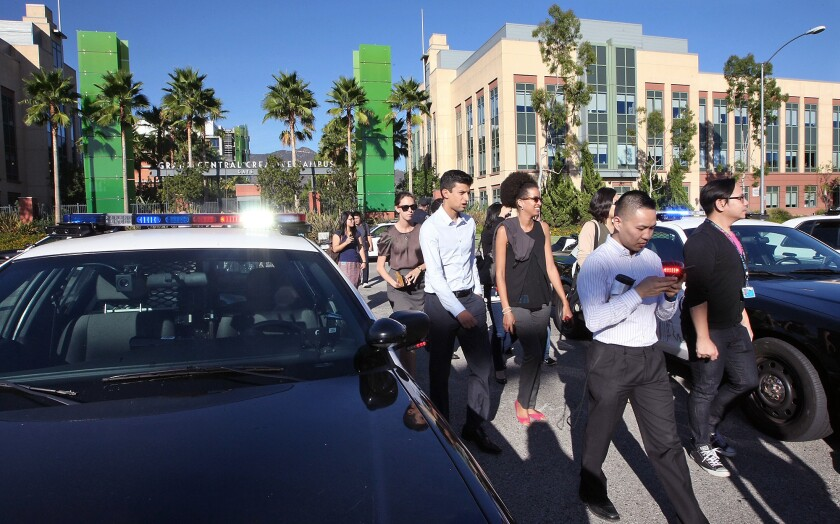 Employees make their way back to work after police cleared KABC following a bomb threat on Wednesday, September 30, 2015. A 22-year-old Glendale man was charged Thursday with making the false bomb threat and another one on Oct. 9, officials said.