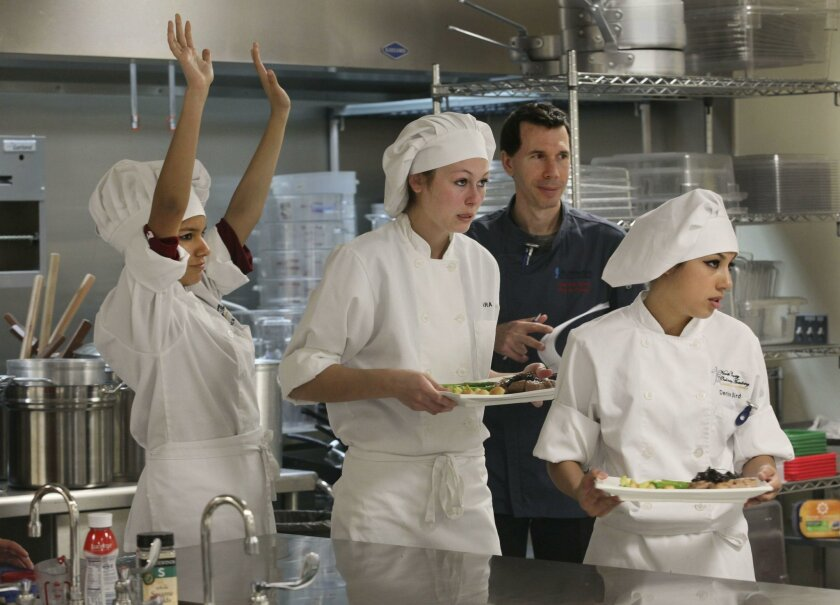 Mission Hills High culinary student Bianca Lopez, left, raises her arms as she completes another phase of her team's culinary competition, and follows teamates Kara Moore, center and Denise Bird, right. Chef  chef Ron Oliver of The Marine Room in La Jolla, looks on as he watches the team head to th