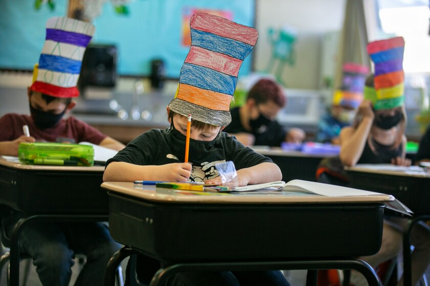 Students sit at desks completing schoolwork while wearing masks and Dr. Seuss hats.
