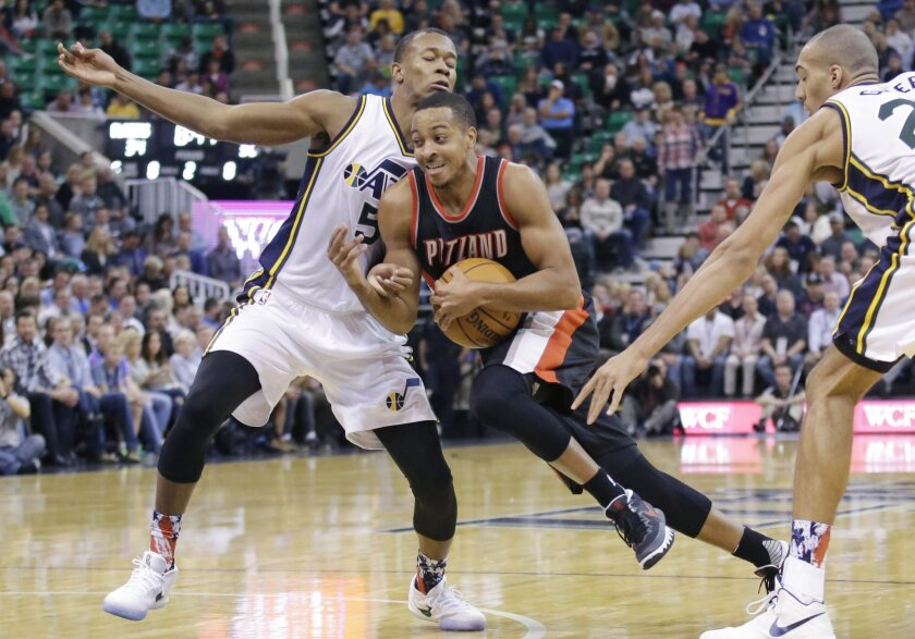 Portland Trail Blazers guard C.J. McCollum, center, drives to the basket as Utah Jazz's Rodney Hood (5) and Rudy Gobert, right, defend in the second quarter during an NBA basketball game Wednesday, Nov. 4, 2015, in Salt Lake City. (AP Photo/Rick Bowmer)