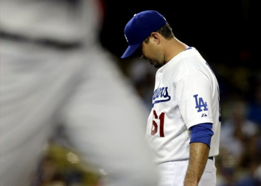 Dodgers pitcher Josh Beckett drops his head after walking Washington Nationals' Bryce Harper Monday night.
