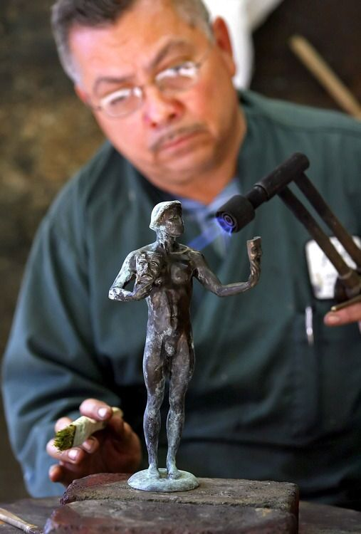 """Patinazation worker Joaquin Quintero shows how he applies patina to the Screen Actor's Guild """"The Actor"""" bronze statue at American Fine Arts Foundry in Burbank on Tuesday, January 25, 2011. The company has been making the 12-lb. SAG statue for 17 years."""