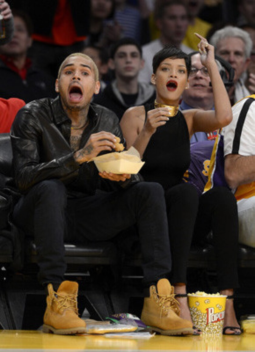 """Rihanna, with Chris Brown at a Los Angeles Lakers game in December, says she's """"happy"""" to be back with Brown."""