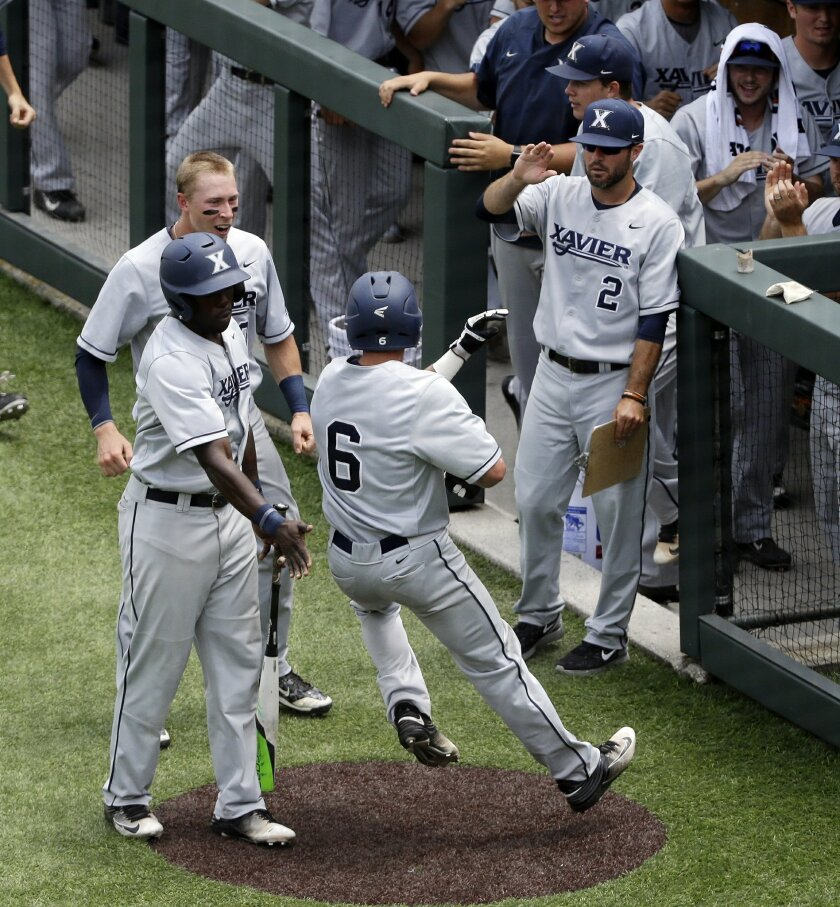 Xavier's Rylan Bannon (6) is congratulated after scoring on a hit by Daniel Rizzie in the fourth inning of an NCAA college baseball regional tournament game against Vanderbilt, Saturday, June 4, 2016, in Nashville, Tenn. (AP Photo/Mark Humphrey)