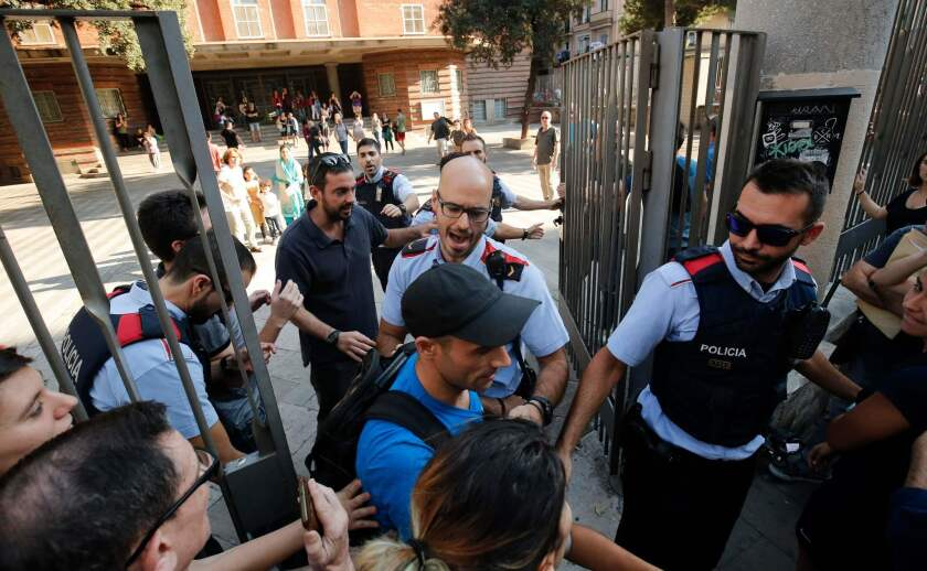 Police officers try stop referendum supporters from going into a school Friday in Barcelona. Pro-separatist Catalans occupied several Barcelona schools designated to be polling stations in a contested independence referendum to ensure the vote will go ahead.