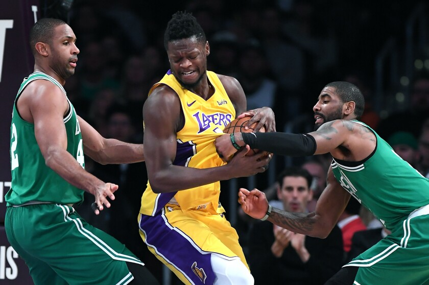 Lakers forward Julius Randle tries to power his way through the double-team defense of Celtics Kyrie Irving, right, and Al Horford during a game last season.