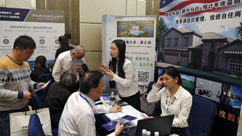 Visitantes chinos buscan información sobre el programa de visas EB-5, del gobierno de los EE.UU., en una cumbre de inversión realizada en Beijing, en 2017 (Andy Wong / Associated Press).