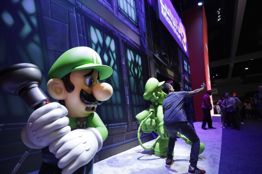 """LOS ANGELES, CA -- JUNE 11, 2019: An attendee takes a picture in front of """"Luigi's Mansion 3"""" during"""