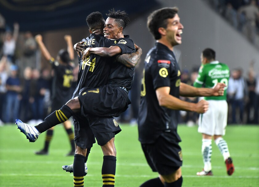 LAFC's Latif Blessing (7) jumps into the arms of teammate Mark-Anthony Kaye as they celebrate their win over León during the CONCACAF Championship League match at Banc of California on Thursday.