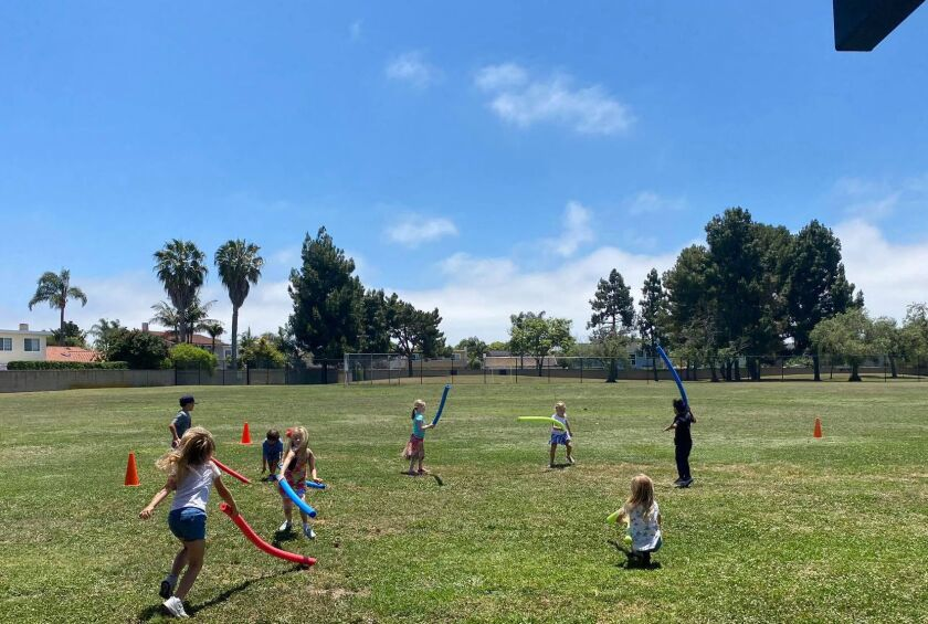 Children socially distance while playing noodle tag at the YMCA Child Care Moffett location in Huntington Beach in May.