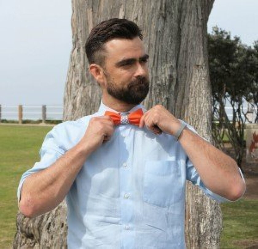 Zach Barnhorst sports one of the bow ties he designed for his company, ZB Savoy Bowtie Co., at Scripps Park. A singer and guitarist, he started designing his own bow ties to wear during performances in early 2012.