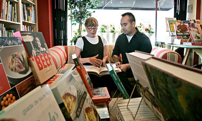 CLOSING: Cook's Library owner Ellen Rose looks over a book with staffer Alan Zumel.