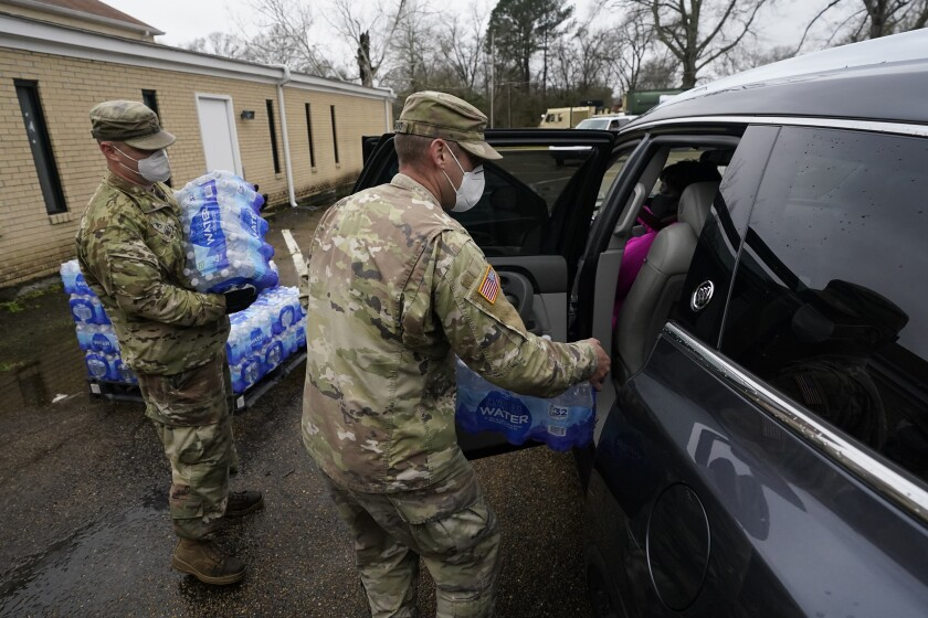 Mississippi Army National Guard Sgt. Chase Toussaint, right, and Staff Sgt. Matthew Riley, both with the Maneuver Area Training Equipment Site of Camp Shelby, place bottled water into a vehicle, Monday, March 1, 2021, at a Jackson, Miss., water distribution site on the New Mount Zion Missionary Baptist Church parking lot. In addition, the guardsmen maintained a tanker with non-potable water for flushing toilets. Similar sites are maintained through the capital city, more than 10 days after winter storms wreaked havoc on the city's water system because the system is still struggling to maintain consistent water pressure, authorities said. (AP Photo/Rogelio V. Solis)