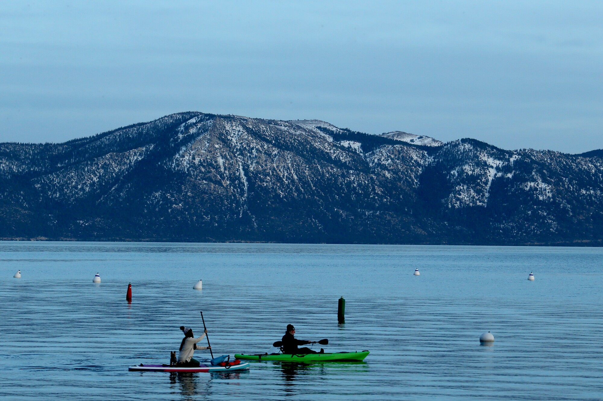 A paddle boarder and a kayaker glide across the surface of Lake Tahoe's frigid waters on Jan. 11.