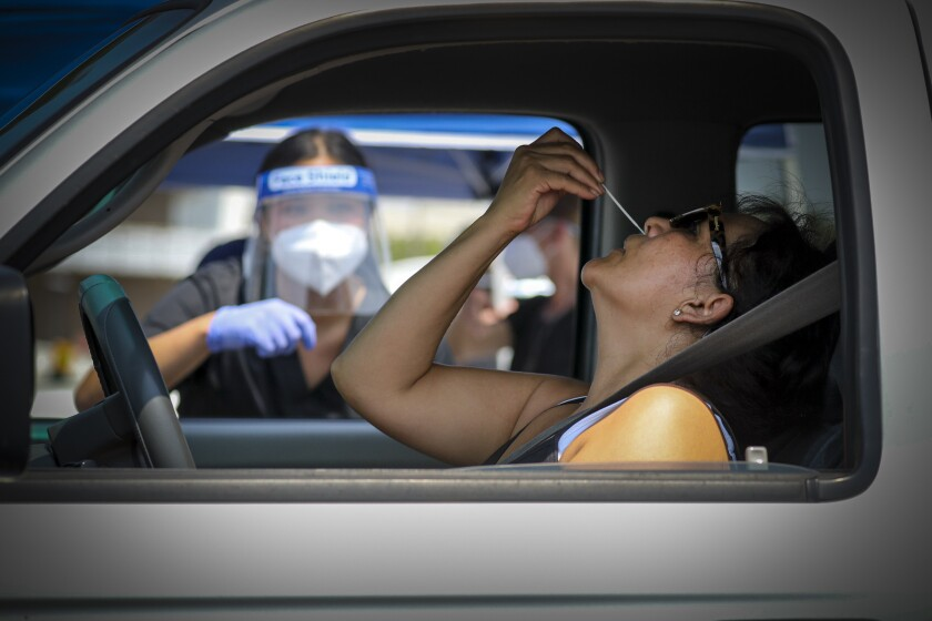 Susana Copca self-swabs at a drive-in free COVID-19 testing site in the Santa Ana College parking lot.
