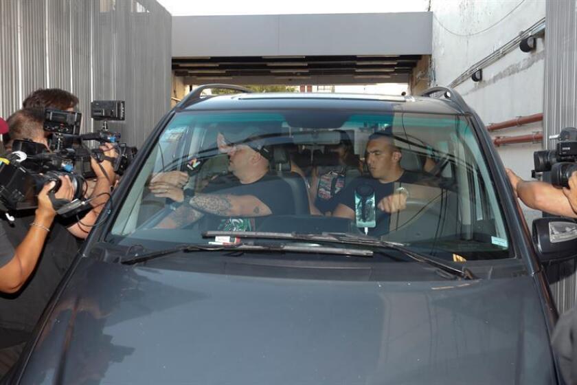 El exfutbolista argentino Diego Maradora (i-atrás, parcialmente cubierto) fue registrado este viernes al responder preguntas de la prensa, desde el interior de un vehículo, mientras salía de la Clínica Olivos, en Buenos Aires (Argentina). EFE