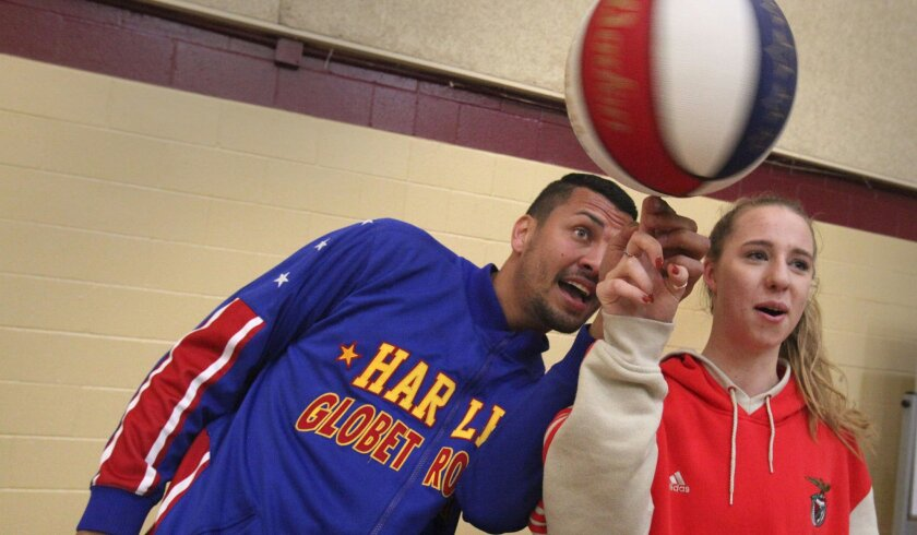 """Harlem Globetrotter Orlando """"El Gato"""" Melendez spins a basketball with student Alessandra Aguirre , 16, after a school assembly at The Bishop's School."""