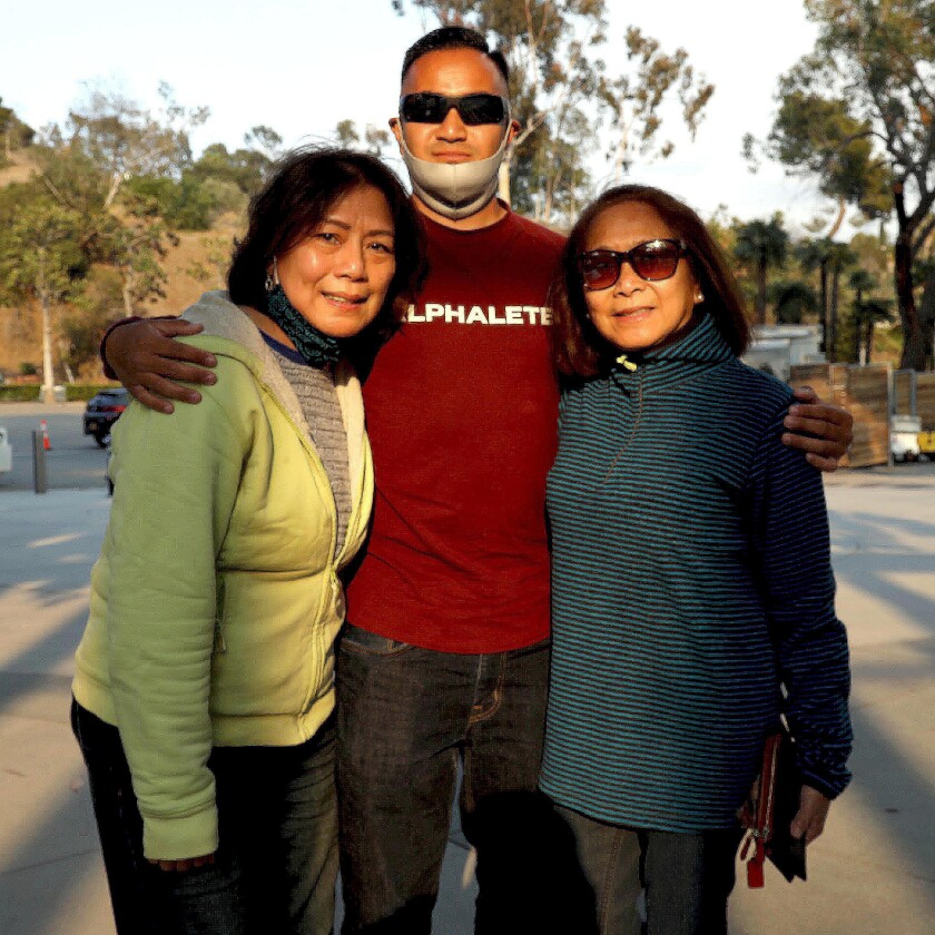 A man and two women pose for a photo.
