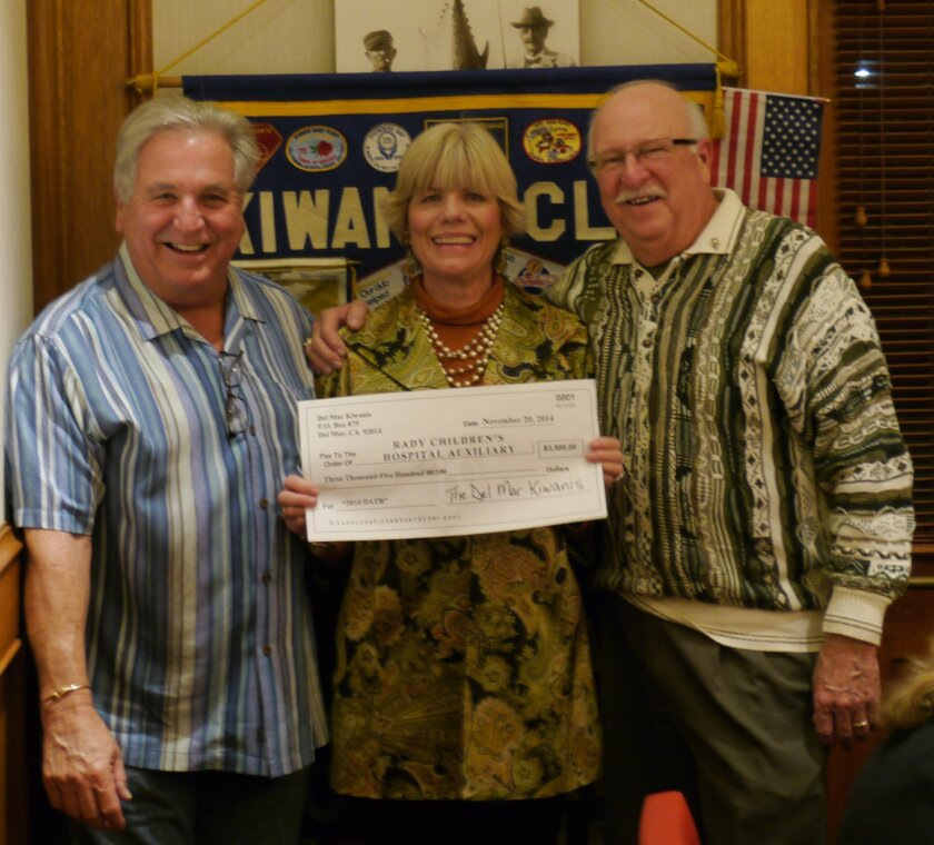 The Del Mar Kiwanis Club President Steve Gardella, left, presents a check for $3,000 to Celebration for Champions representative Marjo Miller (center) as Kiwanis Division 37 Lieutenant Governor Carl Ames looks on.