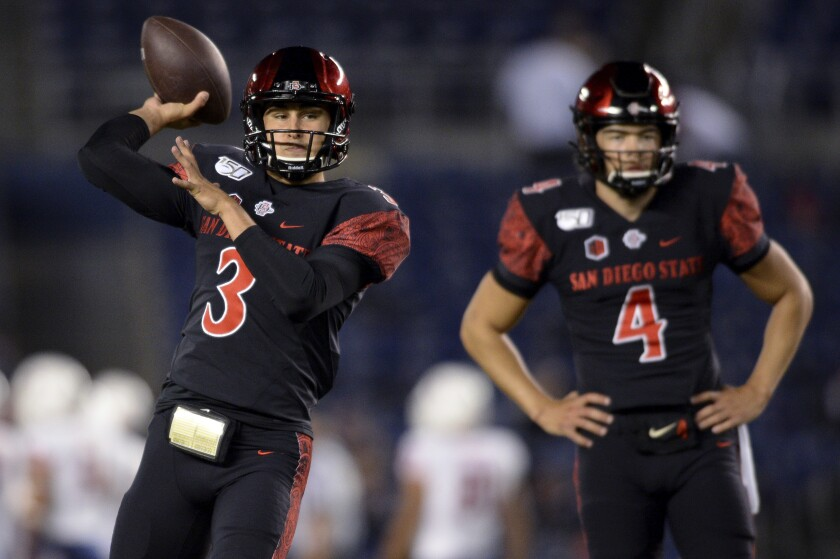 San Diego State quarterback Carson Baker (3) throws as quarterback Jordon Brookshire looks on before SDSU's game against Fresno State. Baker, a redshirt freshman, will get the first snaps of his college career on Saturday night against BYU. Brookshire could play as well.