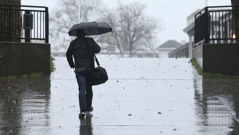 Umbrellas were put to use as a storm moved through Sacramento, Calif., Wednesday, Feb. 13, 2019. Rai