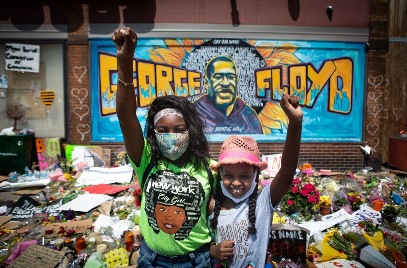 Two girls with fists raised paid respects at the makeshift memorial where George Floyd was killed by Minneapolis police.