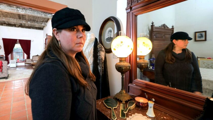 Portrait of paranormal researcher Nicole Strickland in the main bedroom of the Rancho Buena Vista Adobe. She's written a book about the hauntings of the historic dwelling.