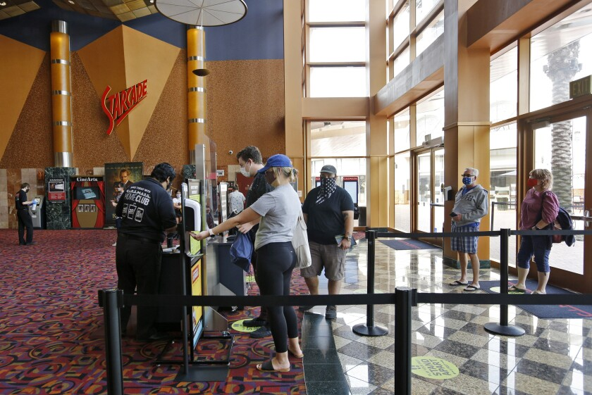 Movie fans buy their tickets minutes after Cinemark Century Cinema opened in Huntington Beach on Friday.