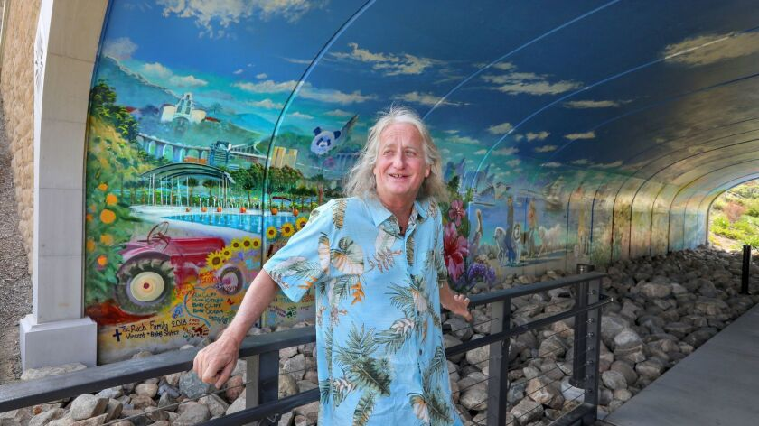 Artist Kevin Anderson, of Encinitas, 60, stands near the entrance to the 72-foot-long mural he painted inside a pedestrian tunnel underneath Via Alta in the Civita project in Mission Valley.
