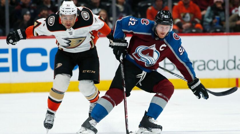 Colorado Avalanche left wing Gabriel Landeskog, right, picks up a loose puck in front of Ducks right wing J.T. Brown in the first period Monday.