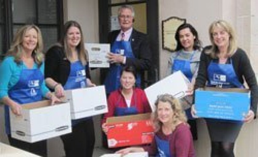 """NSDCAR Realtors hold """"banker's boxes"""" filled with documents ready to be shredded."""