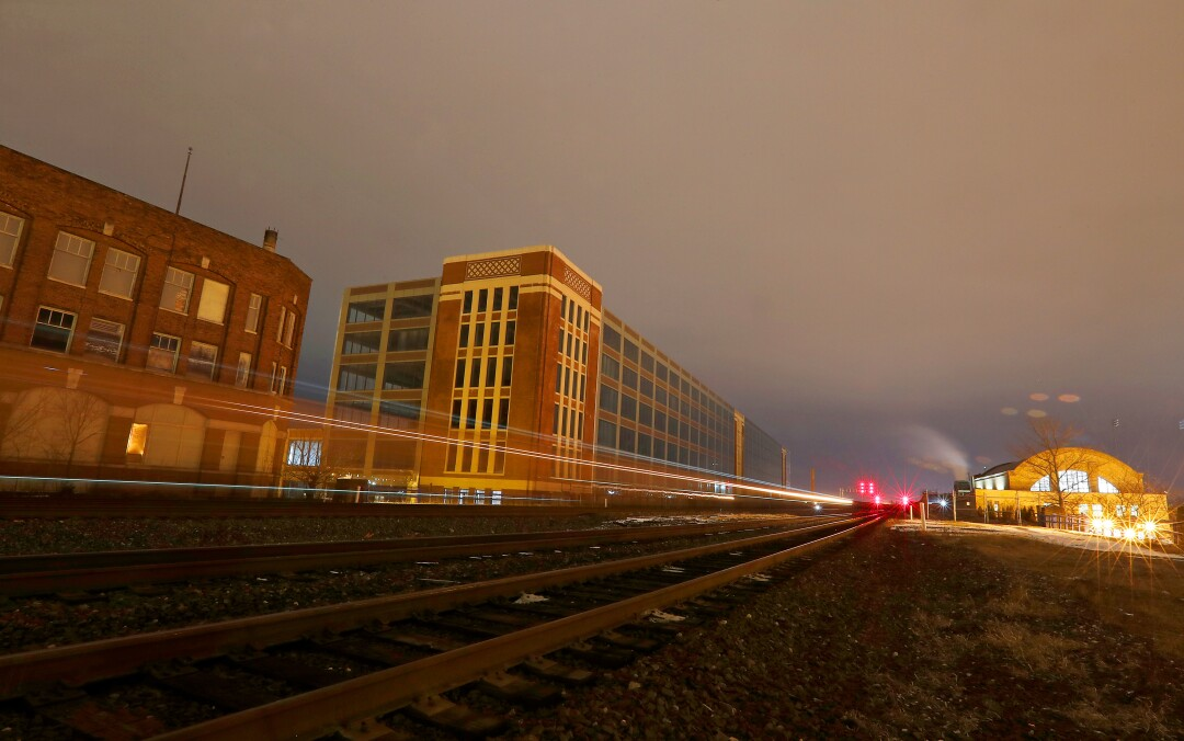 A freight train rolls through South Bend, Ind., between the former Studebaker automobile factory, left, and the old Union Station.