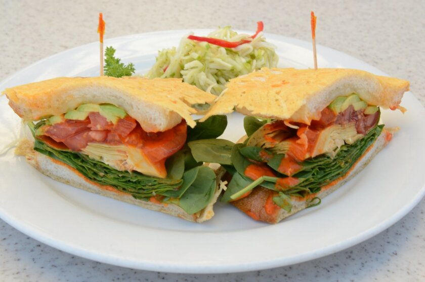 The Veggie Sandwich -- grilled parmesan-crusted bread layered with artichoke hearts, avocado, tomato, spinach, Swiss and roasted red pepper pesto -- with an apple fennel slaw.