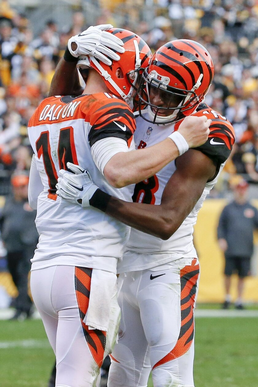 Cincinnati Bengals quarterback Andy Dalton, left, celebrates with wide receiver A.J. Green after throwing him a touchdown pass in the second half of an NFL football game against the Pittsburgh Steelers, Sunday, Nov. 1, 2015 in Pittsburgh. The Bengals won 16-10. (AP Photo/Gene J. Puskar)