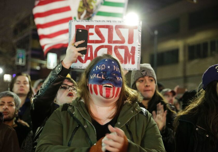 """A woman is pictured with """"No Wall, No Ban"""" painted on her face as people march in support of immigrants and refugees in Seattle, Washington on January 29, 2017."""