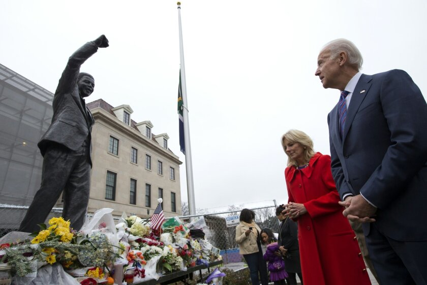"""Vice President Joe Biden, right, and wife Jill Biden, pay their respects to former South African President Nelson Mandela outside the South African embassy in Washington, Monday, Dec. 9, 2013, after signing a condolence book inside. While gazing at a statue of Mandela, Biden said that the former president was, """"the most remarkable man I met in my whole career."""" President Obama is en route to South Africa to attend a Tuesday memorial service for Nelson Mandela. (AP Photo/Jacquelyn Martin)"""