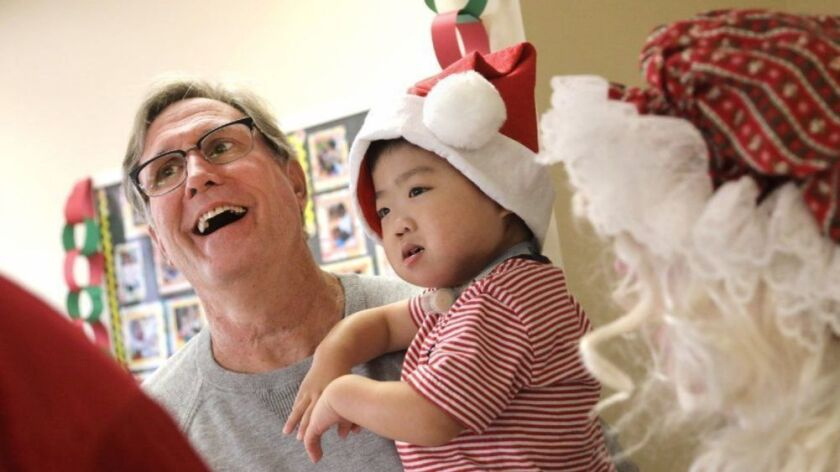 Bob Davis the recreational therapist at the Helen M. Bernardy Center for Medically Fragile Children, guides Lucas Lu, 4, and other children and takes their photo with Santa at the annual Christmas party. This will be his last Christmas with the children as he retires in 2019.