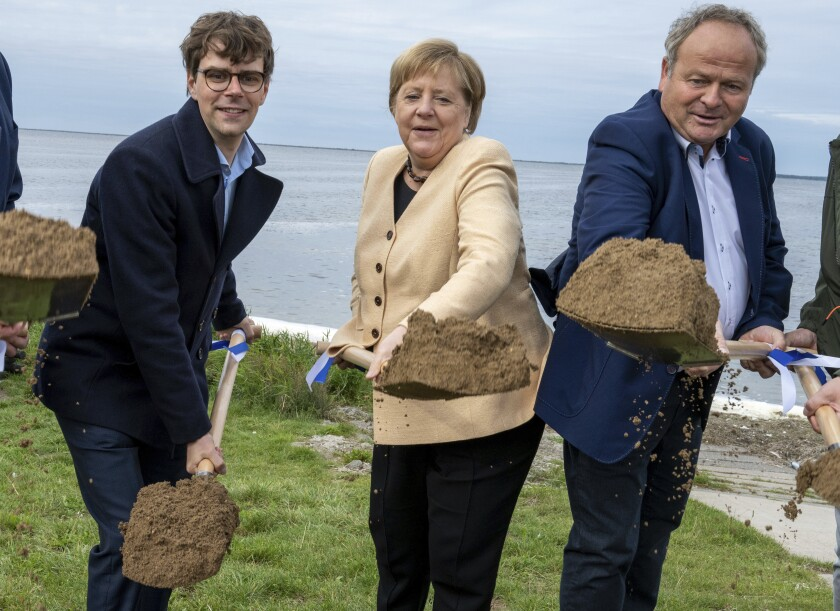 German Chancellor Angela Merkel, center, Georg Guenther, Chairman of the Junge Union Mecklenburg-Vorpommerns and the Mayor of the municipality of Ummanz, Holger Kliewe, right, perform the symbolic ground-breaking ceremony for the extension of the cycle path in the municipality near Waase on the island of Ummanz, Germany, Tuesday, Sept. 21, 2021. (Stefan Sauer/dpa via AP)
