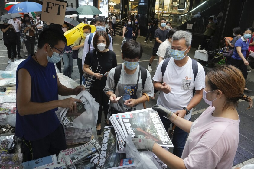 People queue up for last issue of Apple Daily at a newspaper booth at a downtown street in Hong Kong, Thursday, June 24, 2021. Hong Kong's sole remaining pro-democracy newspaper has published its last edition. Apple Daily was forced to shut down Thursday after five editors and executives were arrested and millions of dollars in its assets were frozen as part of China's increasing crackdown on dissent in the semi-autonomous city. ( AP Photo/Vincent Yu)