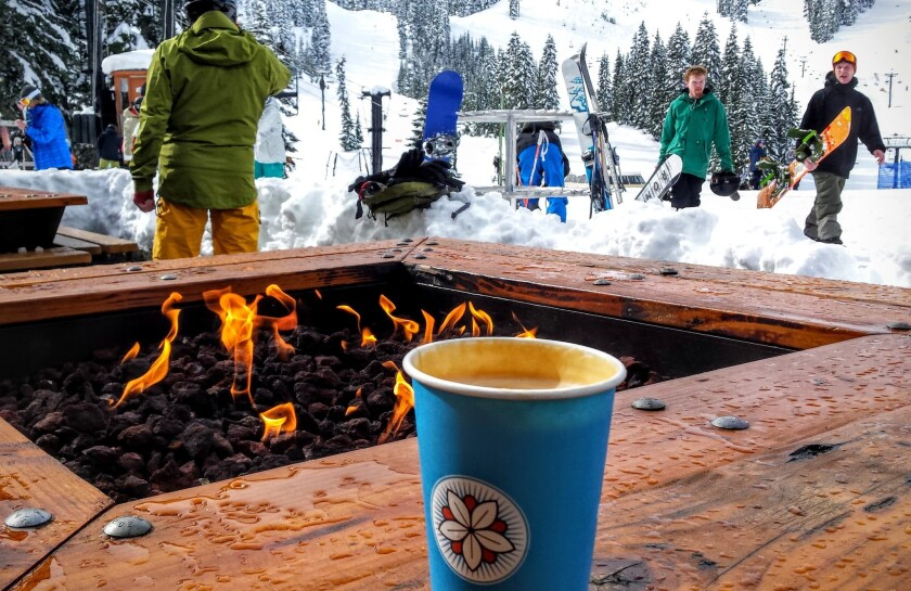 A steaming latte sits on an outdoor fireplace at Granite Peaks Lodge at Stevens Pass.
