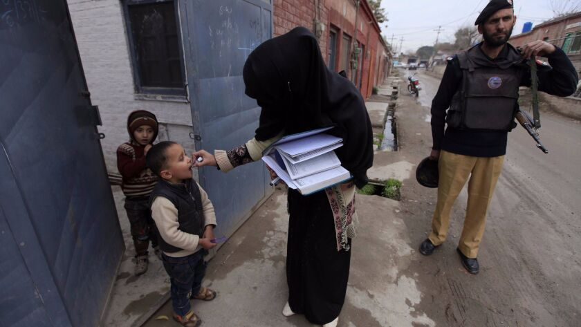 A police officer escorts a polio vaccination team during a three-day countrywide campaign in Peshawar, Pakistan. Attacks by Islamist militants against health workers and police guarding them remained a challenge for a U.N.-funded vaccination campaign.
