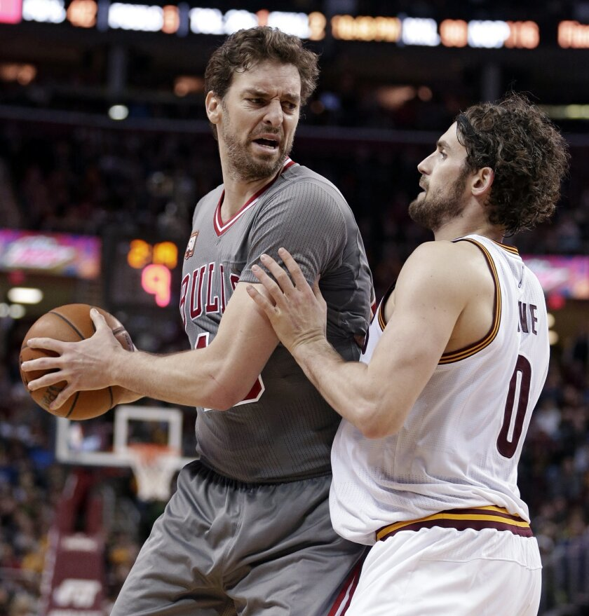 Chicago Bulls' Pau Gasol (16) drives past Cleveland Cavaliers' Kevin Love (0) during the second half of an NBA basketball game Saturday, Jan. 23, 2016, in Cleveland. Gasol scored a team-high 25 points in the Bulls' 96-83 win. (AP Photo/Tony Dejak)