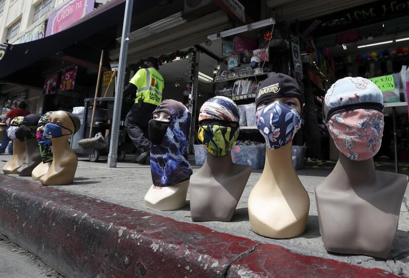 Mannequins wearing protective masks line the sidewalk last week in Los Angeles' Garment district.
