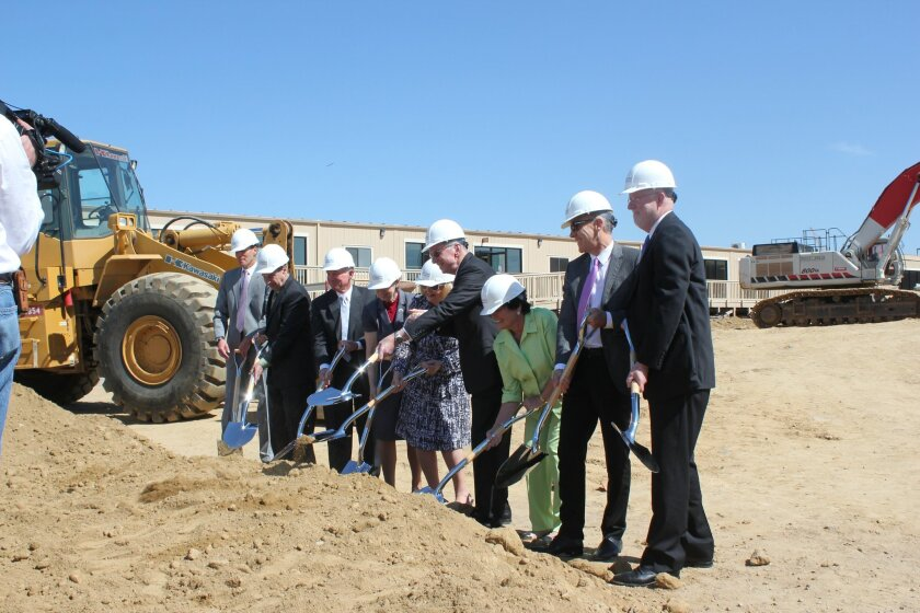 Community leaders open the ground to prepare for three new hospitals on the site.